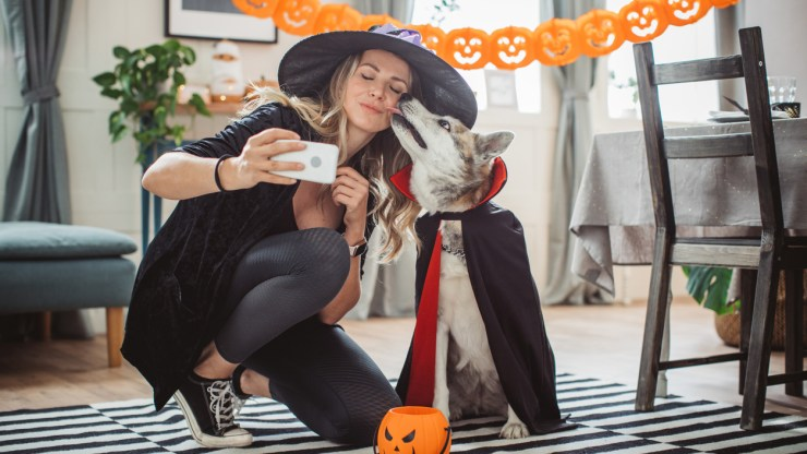 a woman wearing a dog and owner costume for halloween.