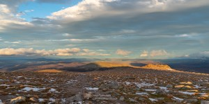 Photo of late sunlight shines on the granite tor just east of the summit of Cairngorm and Bynack More to the left