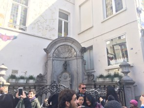 """The Manneken Pis (""""little man pee""""), a bronze sculpture made in 1619, is a popular and very funny tourist attraction. There were probably over 150 people standing in that square looking at the famous sculpture and taking photos."""