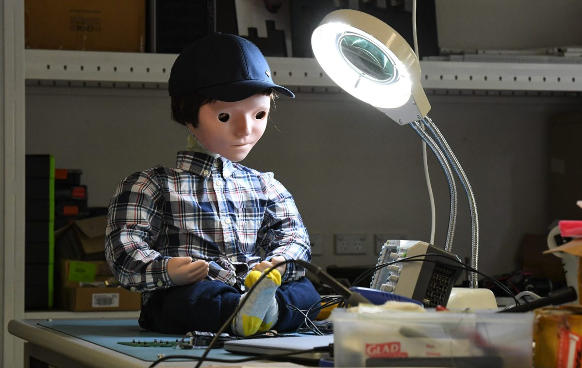 A doll-like robot sits on a workbench in the Creative Robotics Lab, under a bright light.