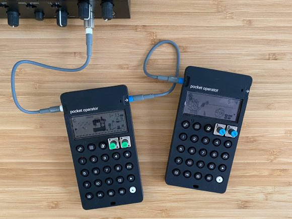 Two black pocket operators which look like small calculators, sit side by side on a wooden desk. They are connected with short grey cables.