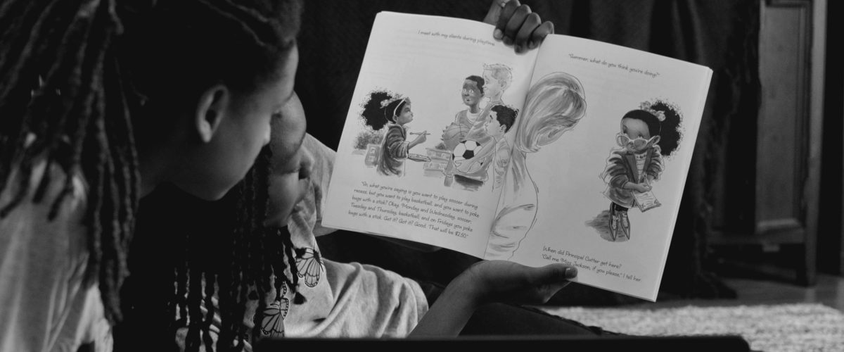 reading a children's book featuring black characters