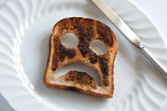 a burnt slice of toast with eyes and a frown cut out of it.