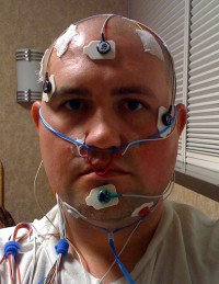 A picture of Scott with all sorts of wires and stickers stuck on his head