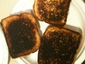 Three burned grilled cheese sandwiches.