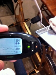 Picture of my Dexcom at 54 mg/dl with double down arrows, bike in the background