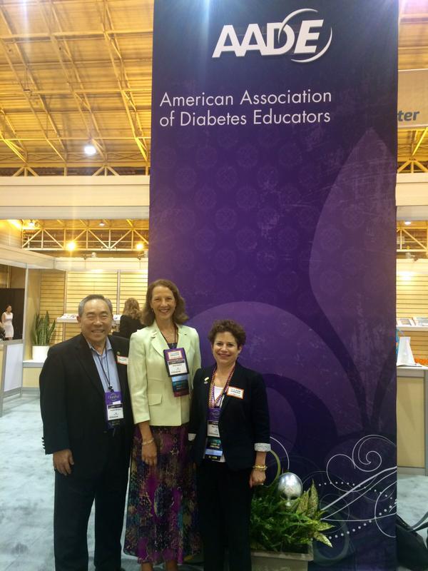 Image of Ken, Karen, and Hope in front of an AADE display