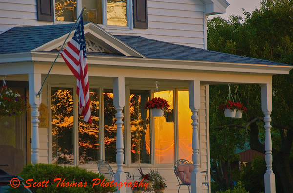 A sunset is reflected in the windows of a house along the Lake Ontario shore near Oswego, New York.
