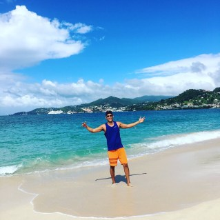 Kevin Wang poses for a photo at Grand Anse Beach, with St. George's in the background.