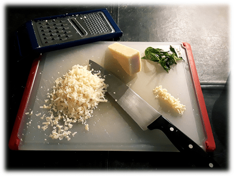 Grated Parmesan cheese, minced garlic, and fresh basil leaves on a cutting board with a French knife and grater