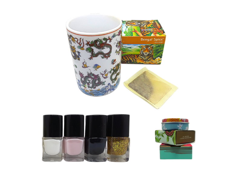 Mug with Chinese dragons, box of Bengal Spice tea, tea bag, white, pink, black, and gold nail polish, boxes of solid perfume