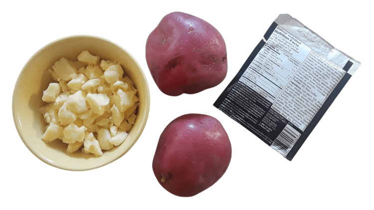 From left to right: crumbled cheese curds in a yellow bowl (about 1 1/2 cups), two large red potatoes, and 1 package of brown gravy mix