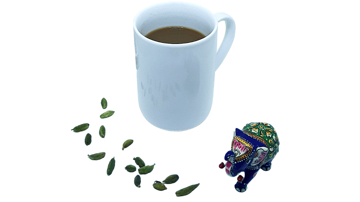 White mug full of coffee surrounded by blue green and pink elephant figurine and cardamom pods