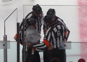 Referee Francis Charron (#6) discusses the Tampa Bay Lightning's waved-off goal with the on-ice crew