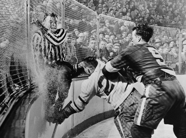 Referee Frank Udvari scales the boards as Detroit's Gordie Howe checks a Toronto Maple Leafs player