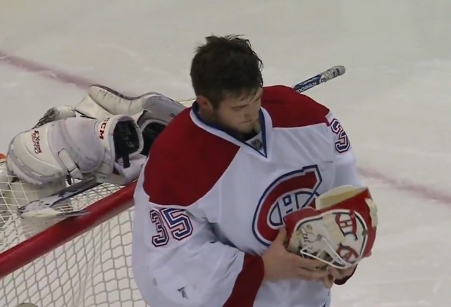 Dustin Tokarski fixes his helmet after giving up a goal to Detroit