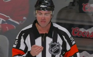 Referee Dean Morton checks the chiclets after being clipped up high by Ondrej Palat's stick