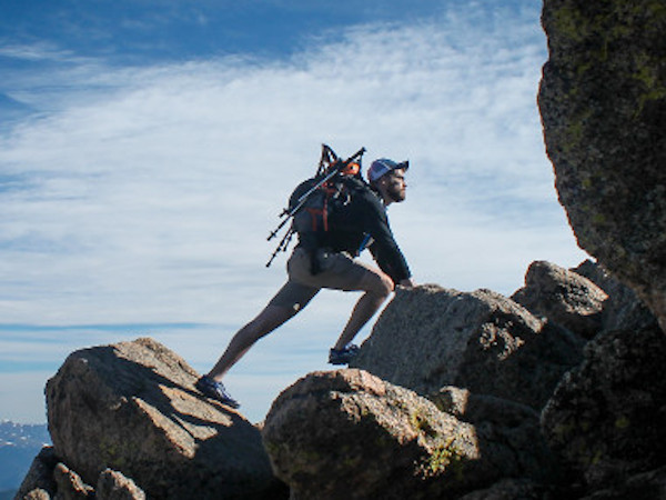 Man climbing rocks with blue sky behind