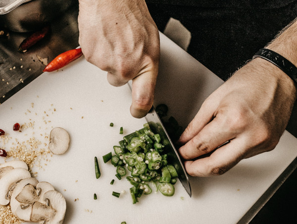 Hands chopping vegetables on a white cutting board