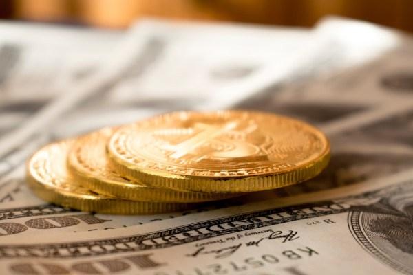 Gold coins on $100 bills