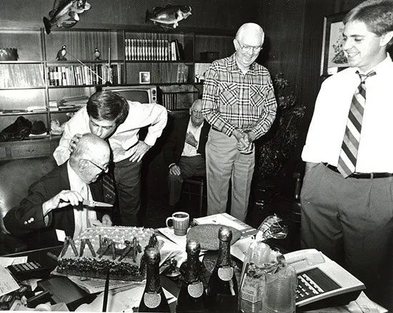 Hubert Osteen, Jr. kisses his father's head, Hubert Osteen, Sr. to celebrate his retirement in 1986. Oldest son Graham Osteen looks on with friends.
