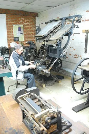 Bill Kinney with Linotype machine in Bennettesville Printing Museum.
