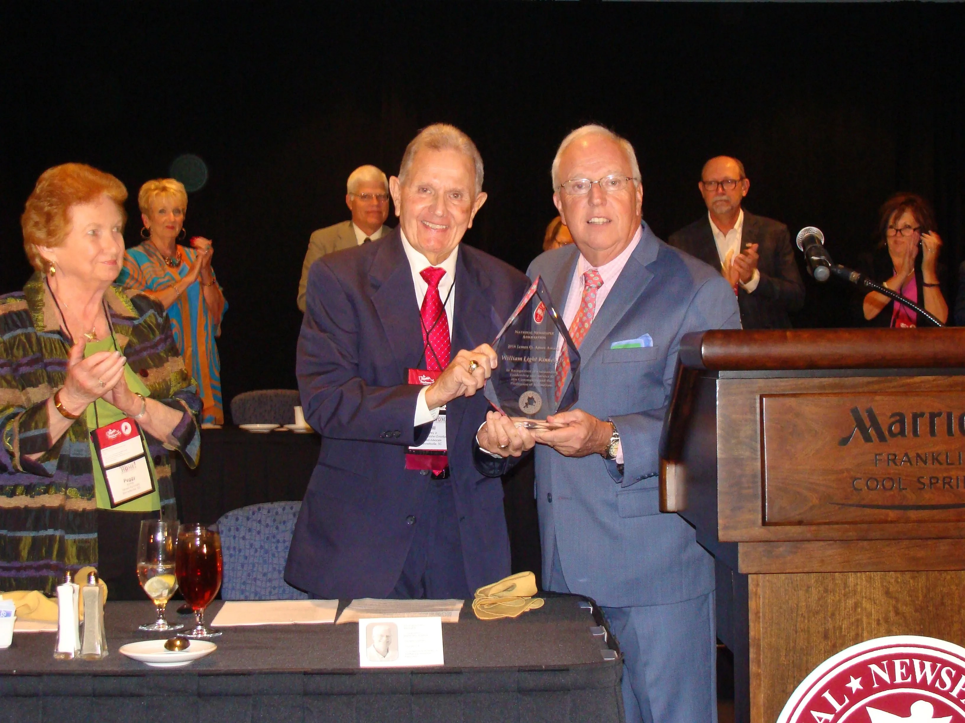 Bill Kinney, center, is presented with the James O. Amos award by NNA President Chip Hutcheson, right, at the 2016 NNA Annual Convention in Franklin, Tenn. Kinney's wife Peggy is on the far left.