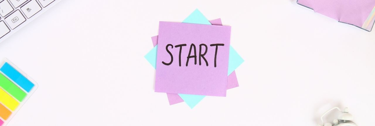 """START"" written on purple sticky note. Sticky note on a desk surrounded by keyboard and other office supplies"