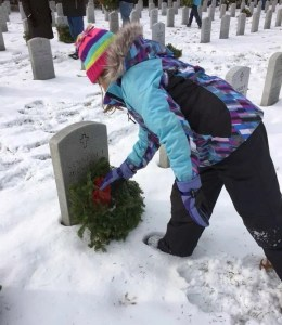 Small child placing a wreath on a veterans grave