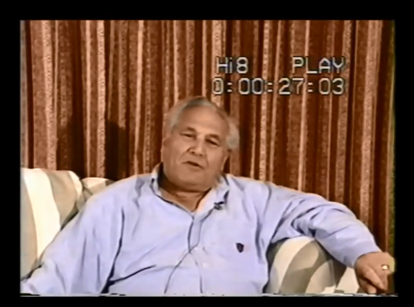 Screenshot of Al Kurbin sitting on a couch, taken from oral history video.