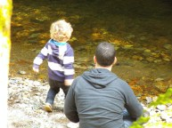 Boy and father throwing stones in water