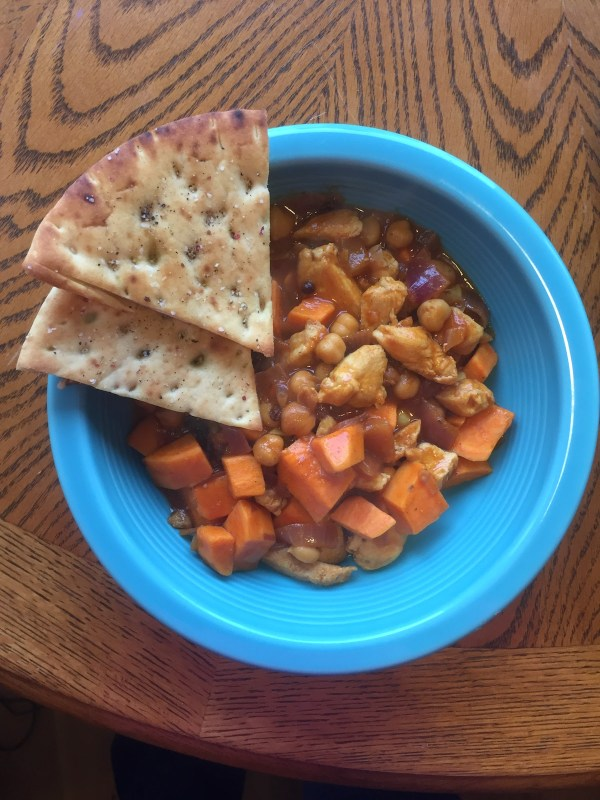 chicken chili with pita bread in a pretty blue bowl on a wood table