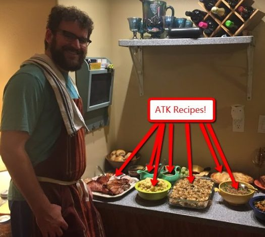 a happy hairy man in an apron with a lot of Thanksgiving food he made