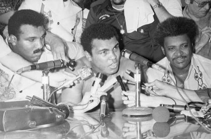 01 Oct 1975, Manila, Luzon Island, Philippines --- Original caption: 10/01/1975-Manila, Philippines- Heavyweight champion of the world Muhammad Ali (C) meets with the press after defeating challenger Smokin' Joe Frazier in the 14th round by TKO. Next to Ali is boxing promoter Don King (R), and Ali's brother Rahaman. --- Image by © Bettmann/CORBIS