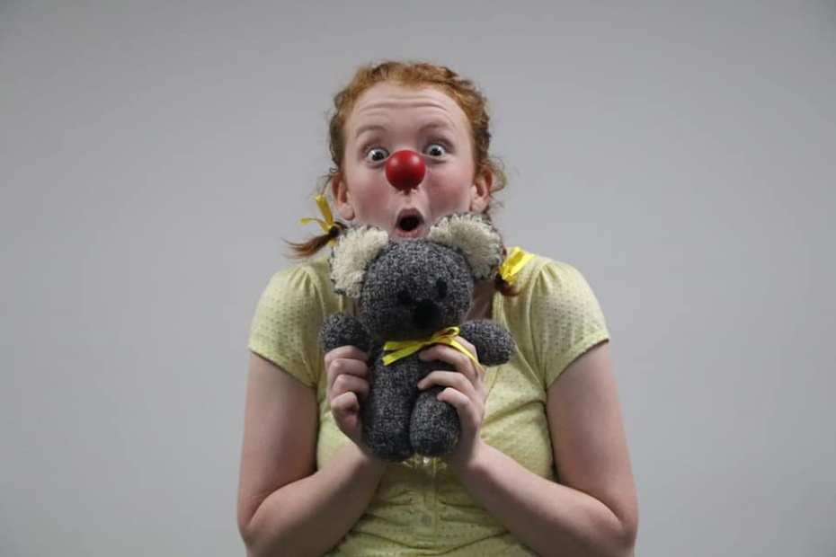 Julie in character for Charlie. Wearing a red clown nose and holding a soft toy up to her face.