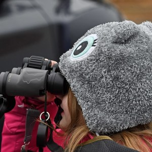 Child wearing a hat is looking through binoculars.