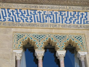"Mudejar architecture: Islamic-Christian co-existence. Arabic characters spell out the phrase ""Nobody is victorious but Allah"", surrounded by Castillian Spanish ""... conquering Don Pedro...""."