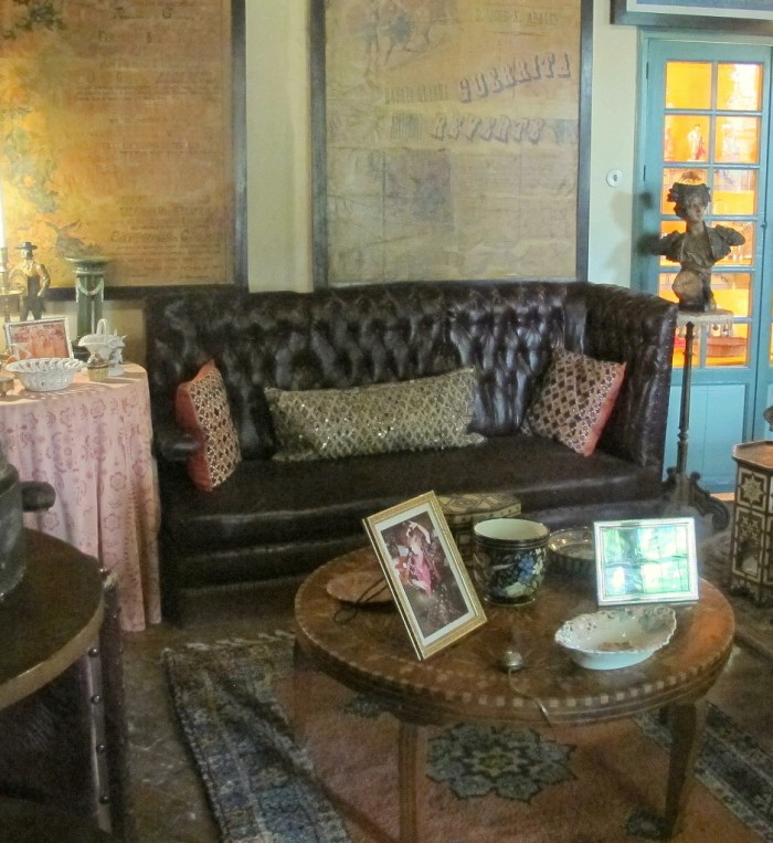 A leather sofa with Indian cushions in the Poster Room.