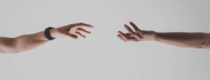 Image showing separation of two hands. It conveys the meaning of social distancing in a photo.