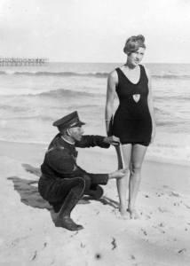 Foto da década de 1920, onde um policial mede o comprimento do maiô que a mulher veste.