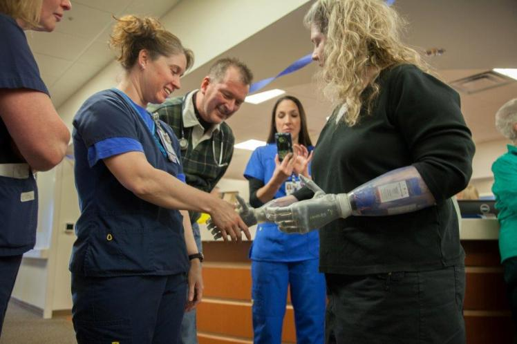 Dr. Scott Biedermann (second from left), the nephrologist on Kuehn's care team, greets her with a smile.