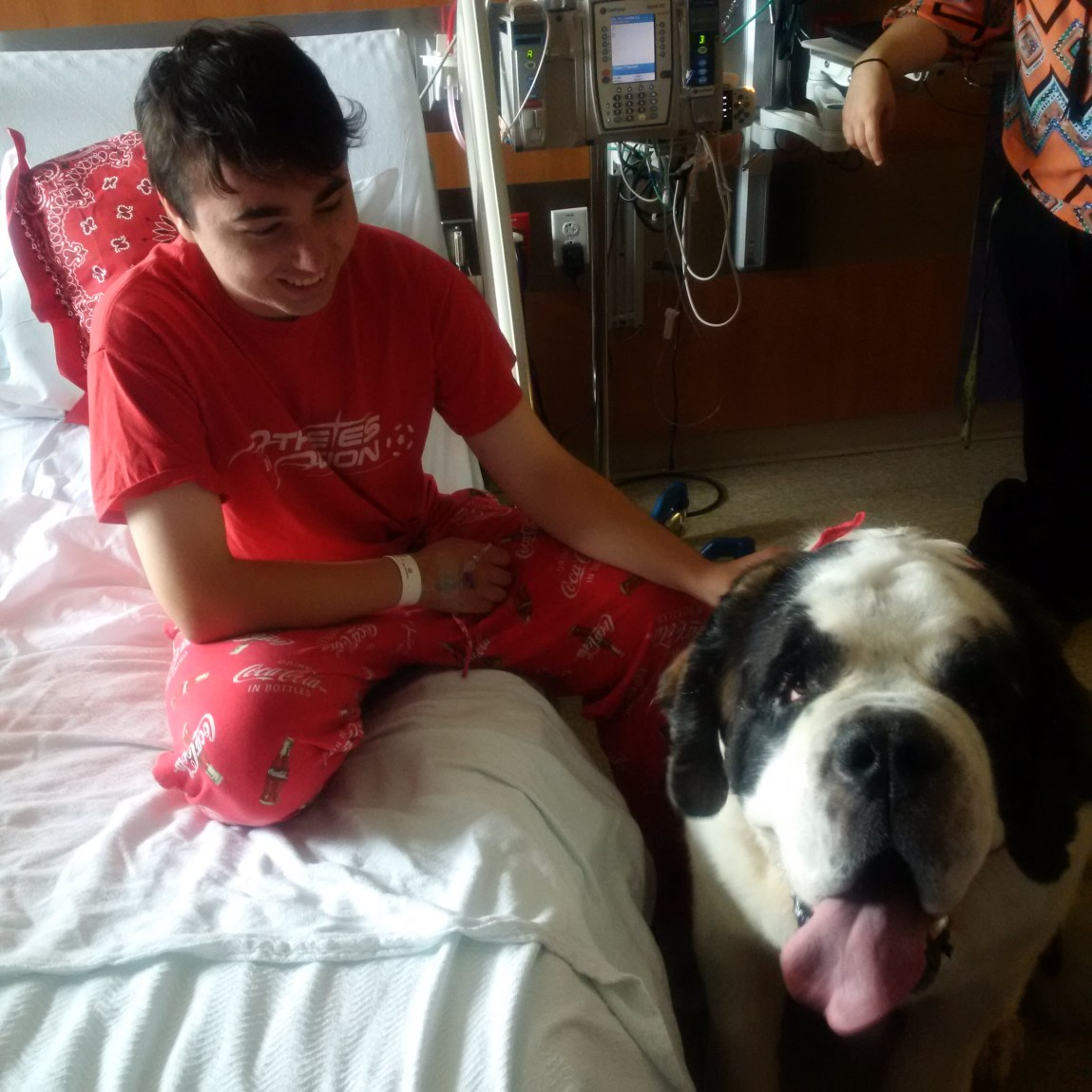 Daniel is visited by one of the therapy dogs at McLane Children's