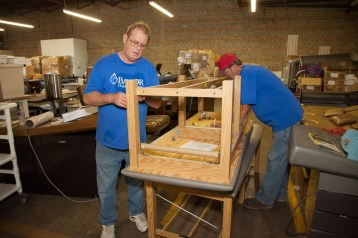 Faith In Action Initiatives volunteers help prepare cargo for shipment