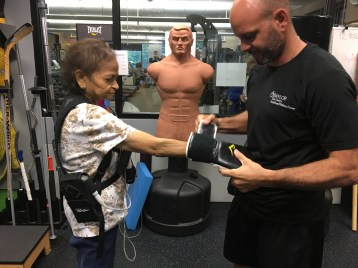 Cardiac rehabilitation patient fastens up for her boxing session