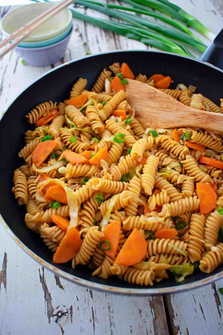 A 45 degree angle view of a frying pan full of pasta stir fry.