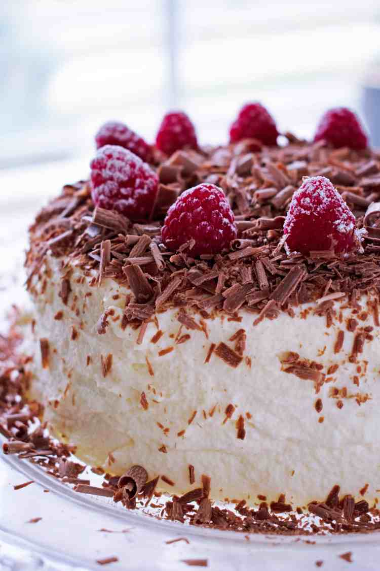 A side view of half a chocolate ripple cake with chocolate shavings and fresh raspberries.
