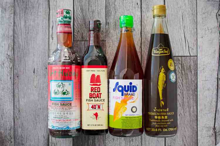 Four bottles of fish sauce laying flat side by side.