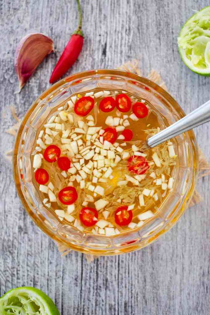 A glass bowl of Vietnamese dipping sauce with chopped garlic, lime pulp and red chillies.