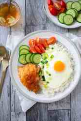 A plate of air fried chicken with fresh vegetables and a sunny side egg on a bed of rice.
