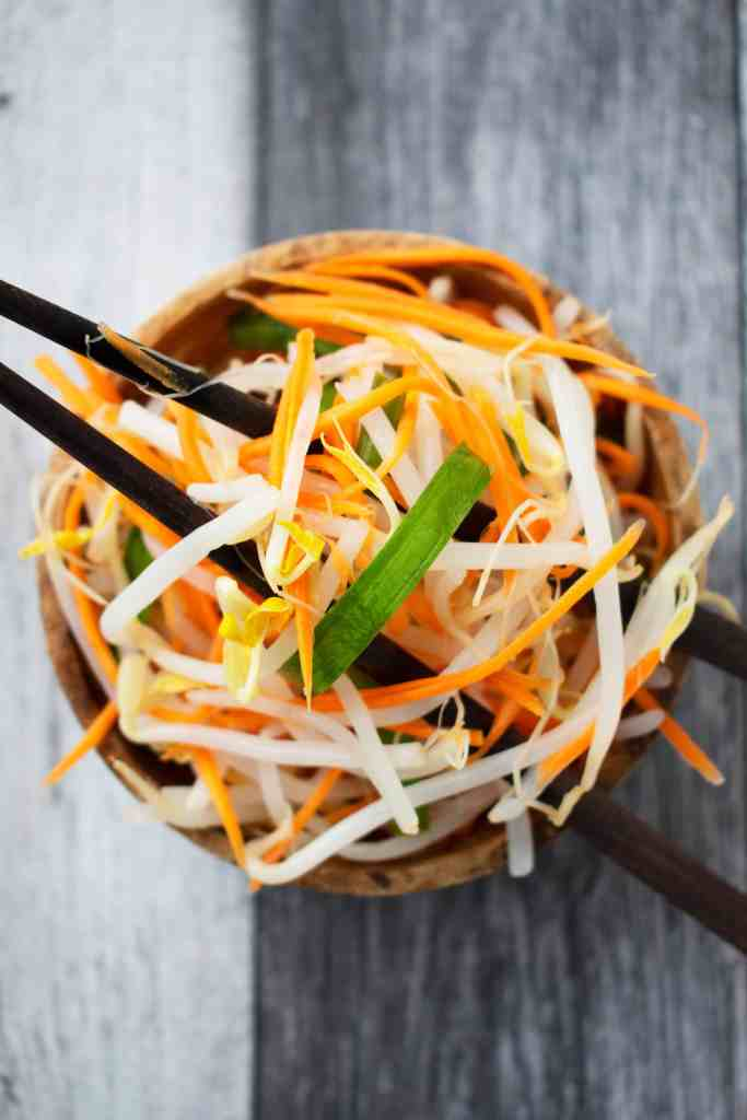 A wooden bowl of pickled bean sprouts with a pair of chopsticks.